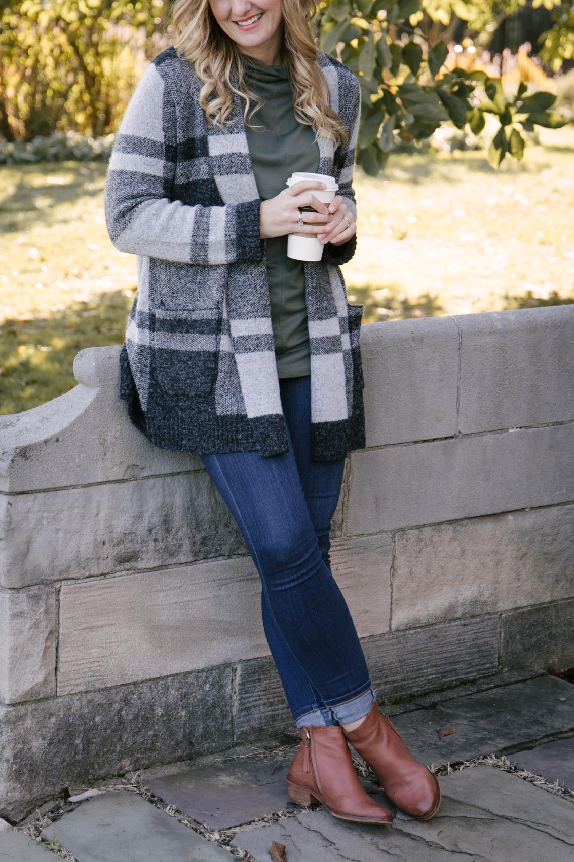 Allyn Lewis styles a casual fall outfit with a cozy plaid cardigan, olive mock neck top, dark wash skinny jeans, and brown leather ankle booties.