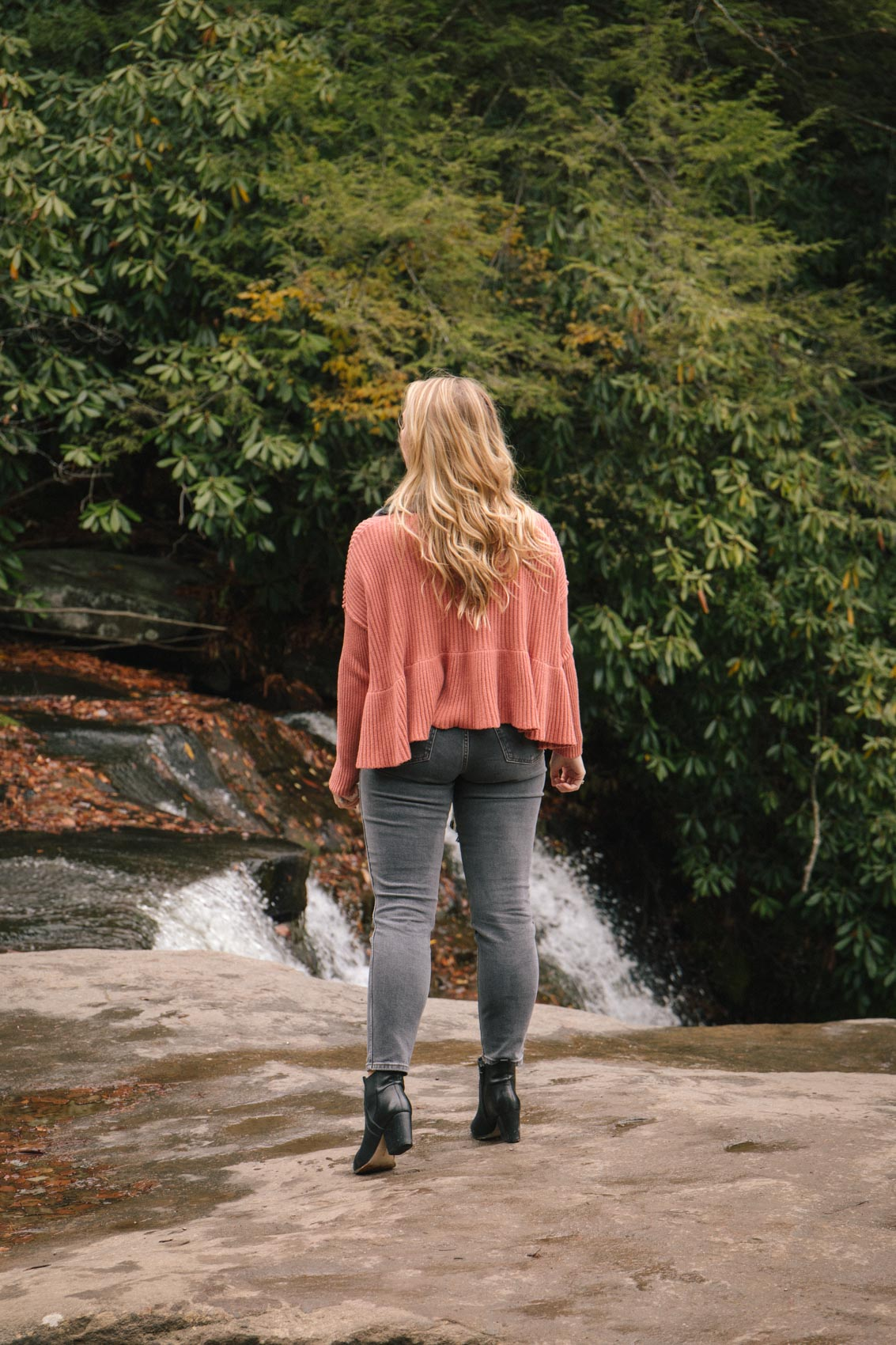woman hiking wearing a trendy pink fall sweater and grey pants
