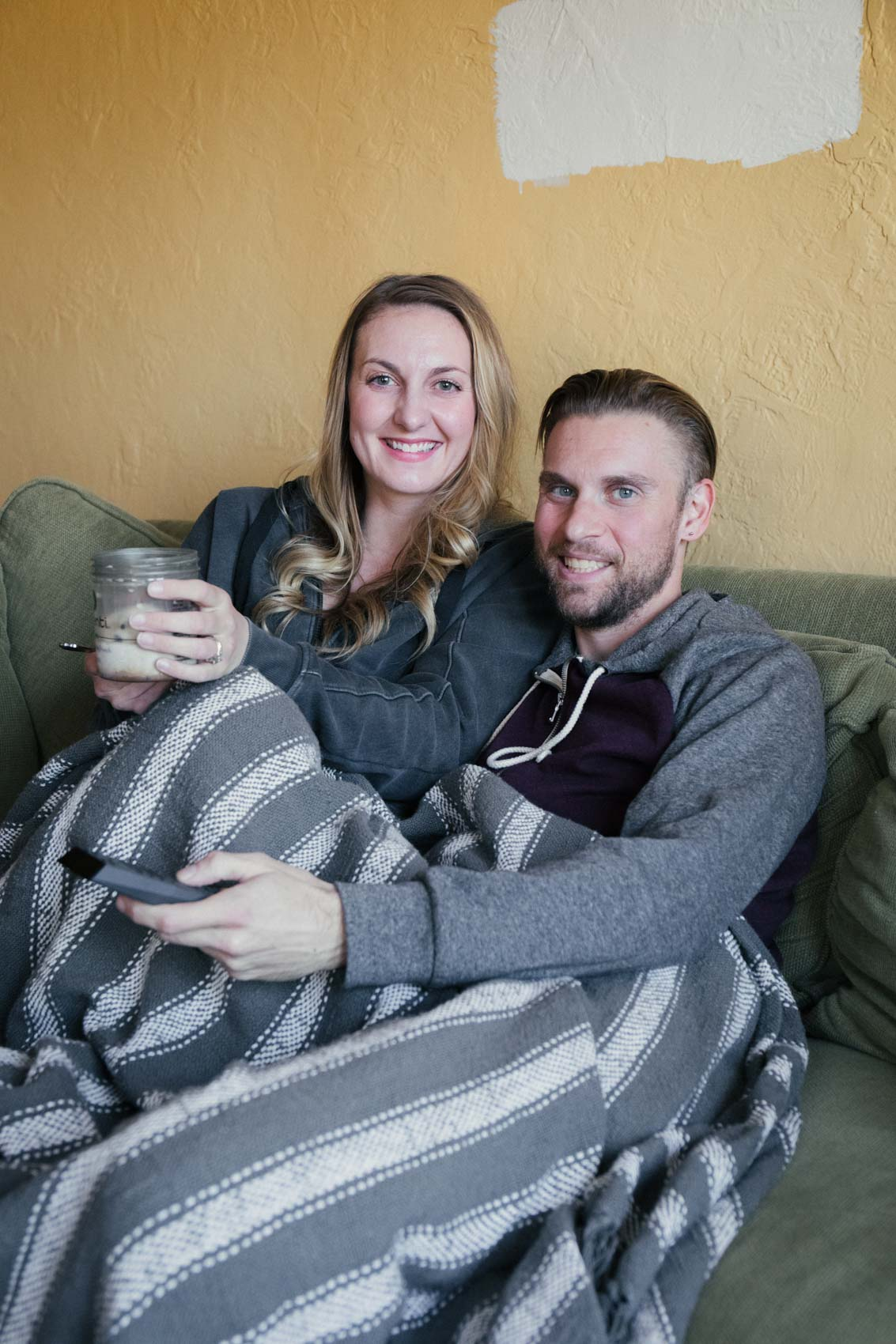 Lifestyle blogger Allyn Lewis snuggled up on the couch for movie night with husband Shaun Novak holding the Xfinity Voice Remote and ice cream